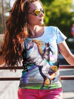 eenhoorn met kat op de rug die aan het schieten is en een regenboog achter zich heeft